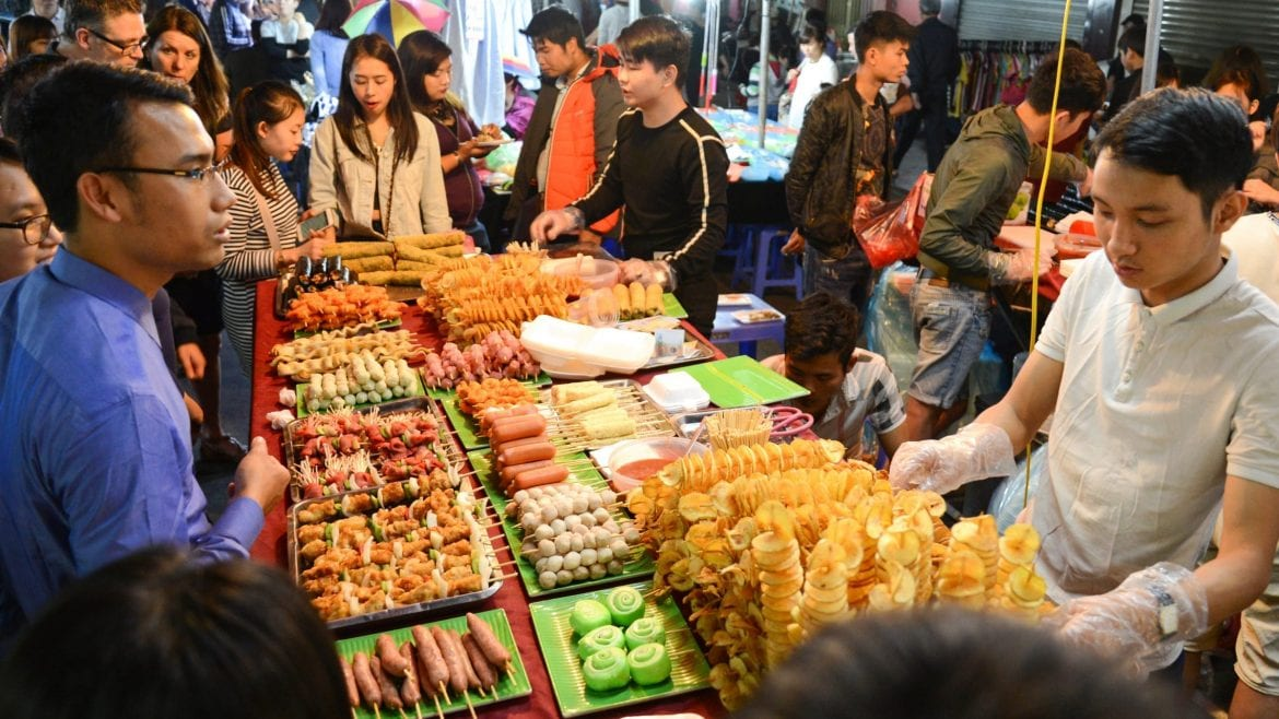 People enjoy treet food at night market, Hanoi, Vietnam, included in tours offered by Asia Vacation Group